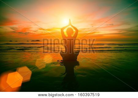 Girl sitting in yoga pose on the sea beach at surreal sunset.