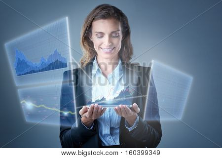 Mature businesswoman looking at holograms transmitted out of her tablet device, showing charts and business trends of stocks