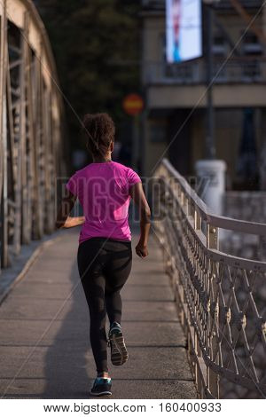 Young sporty african american woman running on sidewalk across the bridge at early morning jogging with city sunrise scene in background