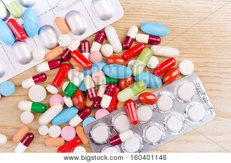 Multicolored capsules and pills lying on a wooden surface. View from Above