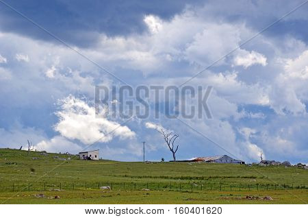 Ominous storm clouds approaching over rolling green hills and farmland in the New South Wales countryside, Australia