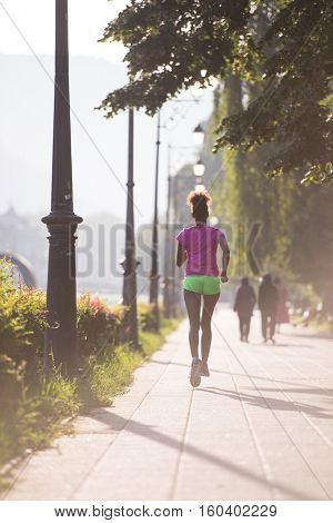 Beautiful young sporty african american woman running at early morning jogging with city sunrise scene in background