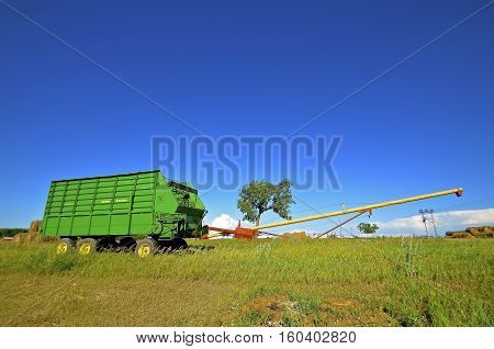 STEELE, NORTH DAKOTA,  JULY 3, 2016: The self-unloading silage wagon is is a product of John Deere Co, an American corporation that manufactures agricultural, construction, forestry machinery, diesel engines, and drivetrains.