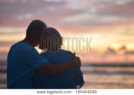 Happy elderly couple rest at tropical beach at sunset, back view