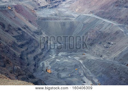 Iron ore opencast mining quarry with lots of machinery at work - view from above