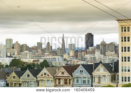 Victorian houses known as the Painted Ladies with downtown in the background as viewed from Alamo Square in San Francisco California