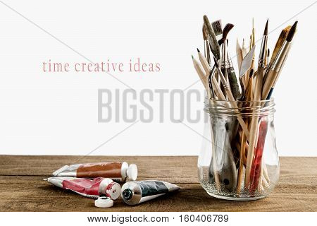 set of different brushes pencils palette knife in the bank next to the oil paints on a wooden table on a white background with the inscription time creative ideas