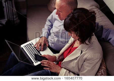 A mid shot from above of two spouses gazing their gadgets, surfing the net, sitting on the couch