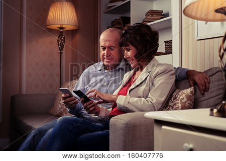 A mid shot of a genial couple looking at their phones, laughing an speaking. Male and female sitting on the sofa, wearing shirt, blouse, jacket and jeans, two lamps surround them