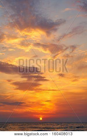 Beautiful sunset in tropical sea. Sun through clouds