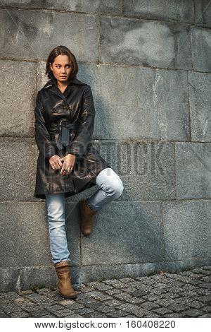 Beautiful young woman near granite stone wall