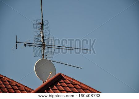 Tv Antennas And Satellite Dish For Television Mounted On The Tiled Roof Of House Isolated On Blue Sk