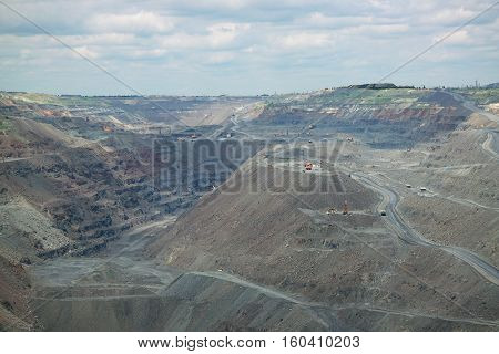 Iron ore opencast mining quarry with lots of machinery at work