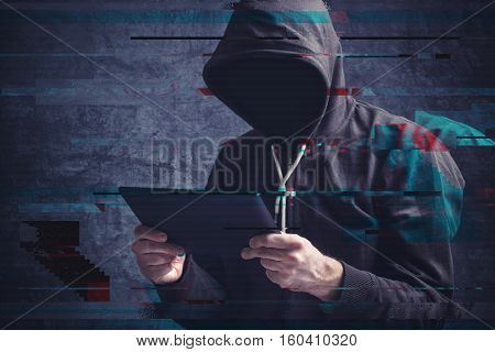 Cyber crime concept with digital glitch effect depicting faceless hooded person with digital tablet computer hacking online accounts
