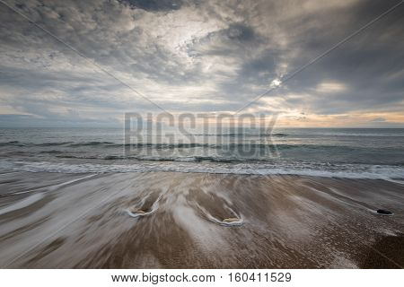 Seahore with pebbles and stormy sky during sunset