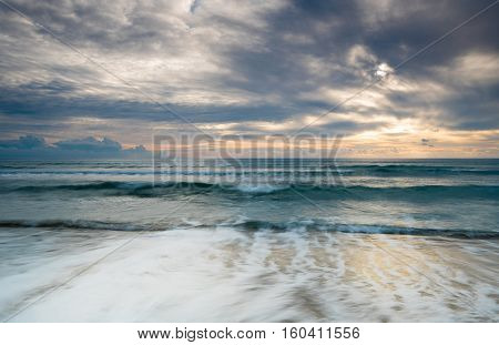 Sea with waves and stormy cloudy sky during sunset