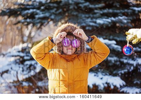 Cute boy in warm clouth and hat catching christmas ball in winter park. Kids play outdoor in snowy forest. Children catch christmas balls