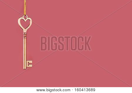 Golden key to hanging on a golden thread on a pink background