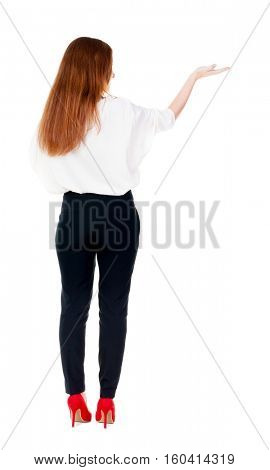 Back view of Beautiful business woman in suite looking at wall and Holds  hand up.  young brunette girl standing. Rear view people. Isolated over white background.