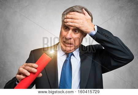 Businessman holding a dynamite stick, financial risk concept