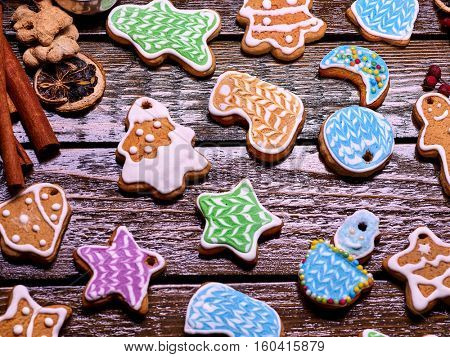 Glazed Christmas cookies on a wooden table serve as a background.