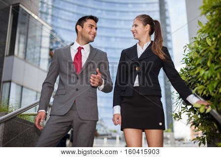 Smiling business people talking while walking down the stairs after work