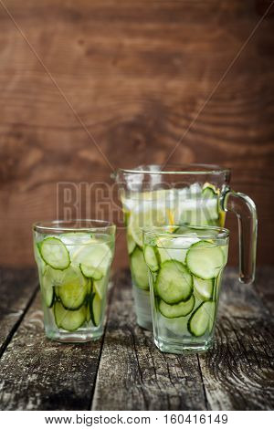 Detox water with cucumber and lemon in a pitcher and two glasses on wooden background.