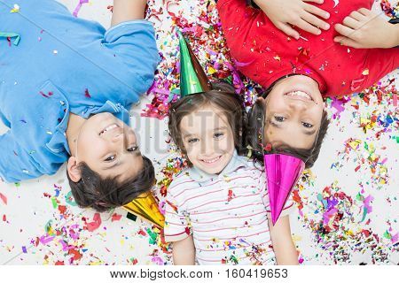 Happy kids celebrating party with blowing confetti top view
