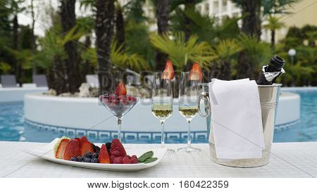 Beautiful arrangement of colorful raspberries, blueberries and blackberries with a bottle of champagne near the swimming pool