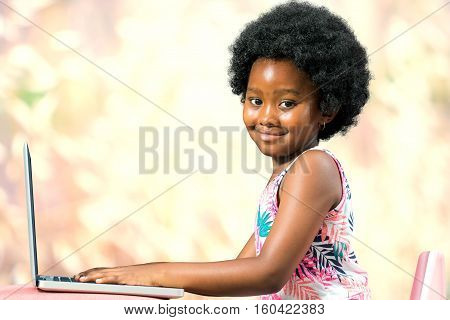 Close up portrait of little african girl with afro hairstyle typing on laptop against colorful background.