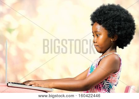 Close up portrait of cute little african girl with afro hairstyle typing on laptop against colorful background.