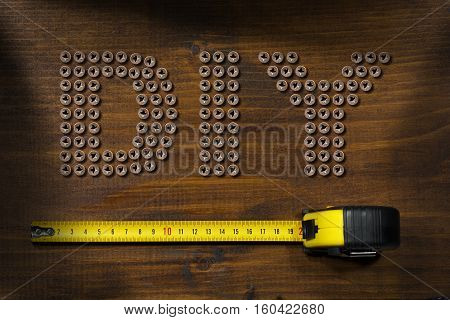 Screws in the shape of text Diy (Do it yourself) on a wooden work table with a yellow and black tape measure