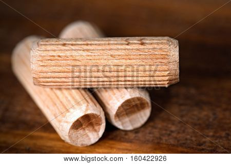 Macro photography of three wooden dowels on a dark wooden work table