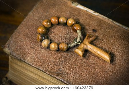 Tau wooden cross in shape of the letter t (religious symbol of St. Francis of Assisi) with rosary bead on an old Holy Bible