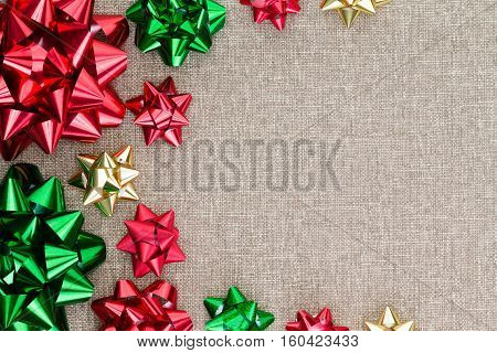 Colorful Christmas foil bow background on burlap with a neat symmetrical arrangement in different sizes as a side border on the textured hessian textile with copy space