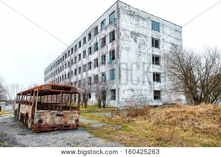 old abandoned high-rise building with burned bus on gloomy cold autumn day