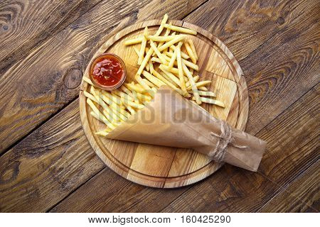 Potato french fries wrapped in craft paper. Fast food take away on rustic wood. Fried potatoes with tomato sauce. Chips with ketchup. Top view
