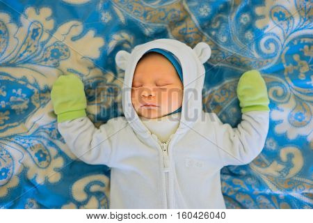 Baby sleeping on the bed. newborn baby boy two weeks old. Baby dressed in warm clothes and gloves. Sweet dream baby.