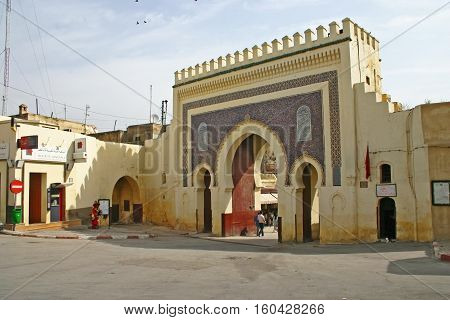 FEZ MOROCCO - MAY 19 2006: Pedestrians walk through the Bab Bou Jeloud (or Blue Gate) the main entrance into the old medina Fes el Bali in Fez Morocco. The Moorish-style gate was built in 1913.