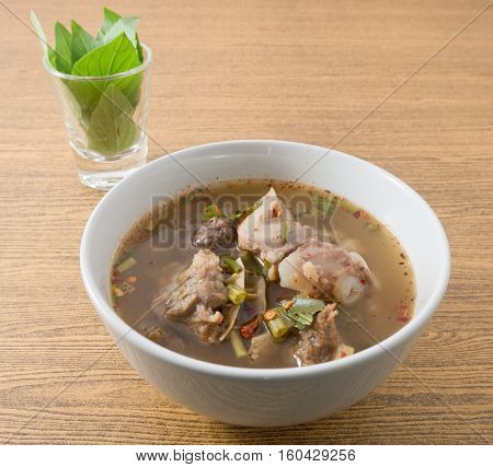 Thai Cuisine and Food A Bowl of Delicious Thai Clear Spicy Hot and Sour Soup with Beef Entrails.
