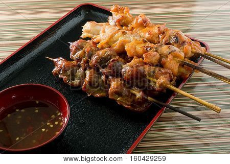 Food and Cuisine Chicken Grilled or Barbecue Chicken on Bamboo Skewer Served with Spicy Sauce.