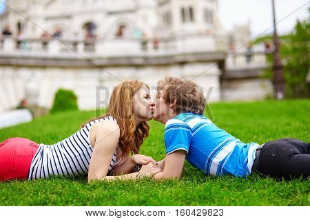 Happy Young Couple Lying On The Grass And Kissing