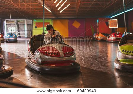 Happy young woman driving a bumper car at amusement park