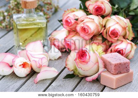 Still life with Rose and care products for a Spa treatment on a wooden Table