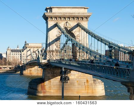 Massive pillar of Szechenyi Chain Bridge over Danube River joins Buda and Pest side of Budapest the capital city of Hungary, Europe. Suspension type of a bridge on sunny day with clear blue sky background.