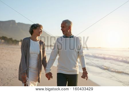 Loving Senior Couple Strolling Together On The Beach