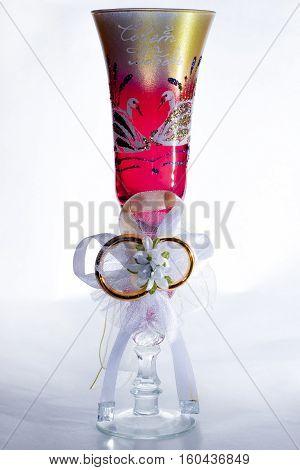 Свадебный бокал с золотыми кольцами и лебедями, на белом фоне.