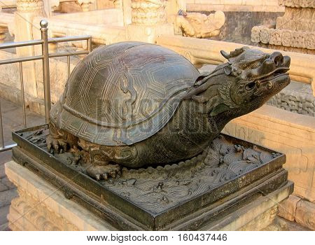 macro photo with the sculpture of the figure of a Turtle with a Dragon's head as a symbol in ancient Chinese culture at the Palace of Heavenly Purity in Beijing (China)