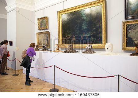 St Petersburg, Russia, Dec 1, 2016: People look at the stuffed heads of owls near painting in Hermitage  Exhibit of temporary modern art exhibition