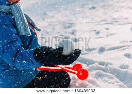 little boy holding snowball in winter nature, kids play snow